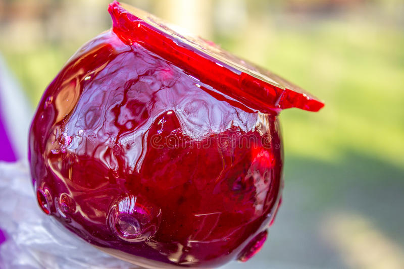 GLAZED APPLE. Delicious red apple glazed with melted sugar royalty free stock image