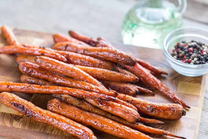 Glazed carrots. On the wooden board: top view stock image