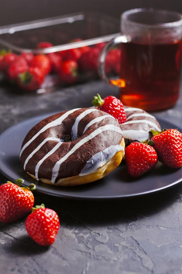 Glazed chocolate donut with strawberry on black plate and cup of tee over dark grey background royalty free stock photography