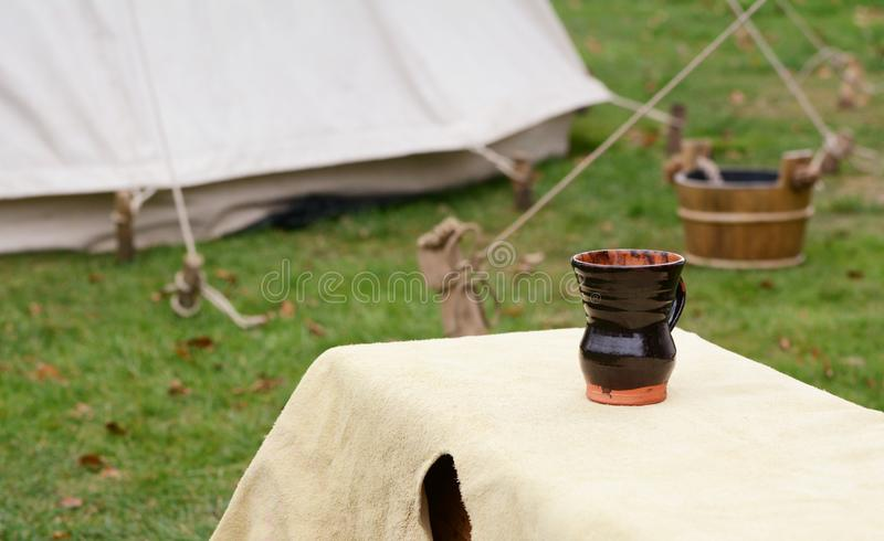 Glazed clay cup on a bench in a Medieval camp stock image