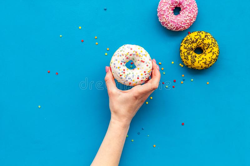Glazed decorated donut in hand for sweet break on blue background flat lay copy space stock photography