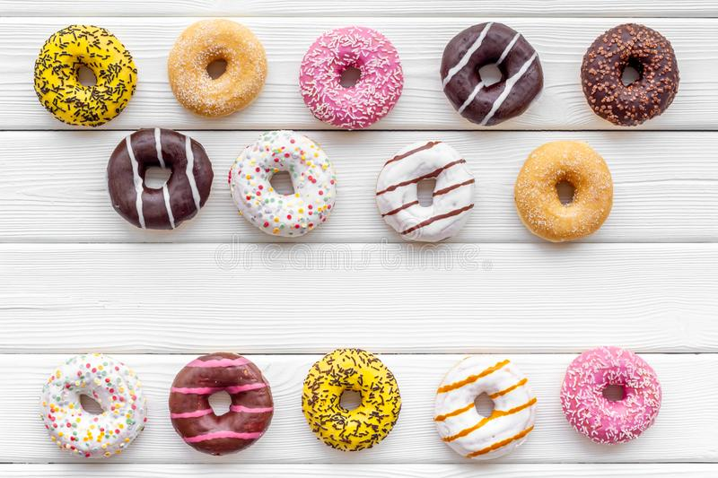 Glazed decorated donuts for sweet break on white wooden background flat lay. Modern pattern. Glazed decorated donuts for sweet break on r white wooden ed stock photography