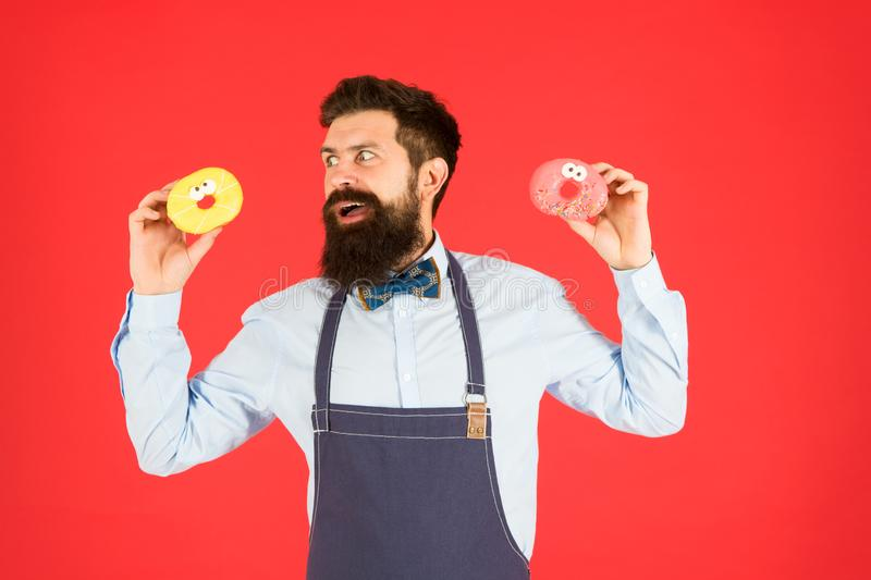 Glazed donut. Bearded well groomed man in apron selling donuts. Donut food. Baked goods. Sweets and cakes. Junk food. Hipster bearded baker hold donuts. Sweet stock image