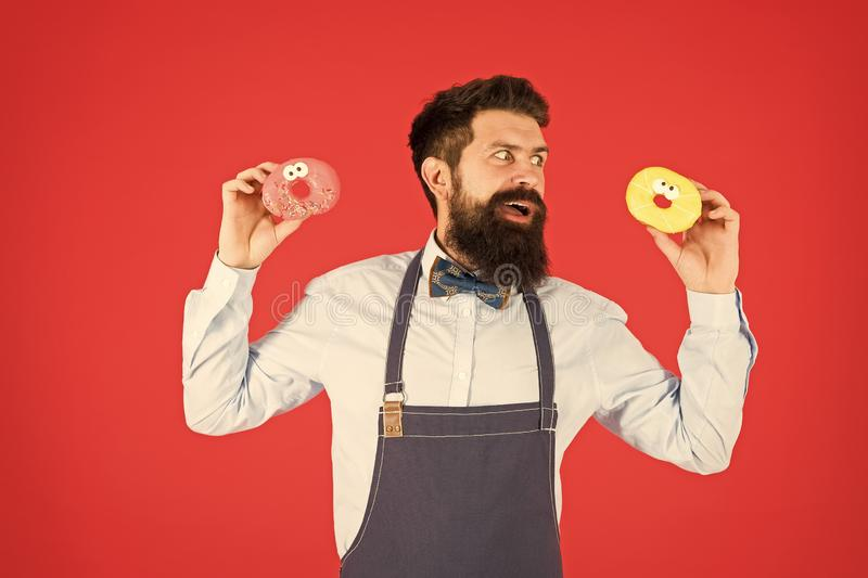 Glazed donut. Bearded well groomed man in apron selling donuts. Donut food. Baked goods. Sweets and cakes. Junk food. Hipster bearded baker hold donuts. Sweet royalty free stock photo