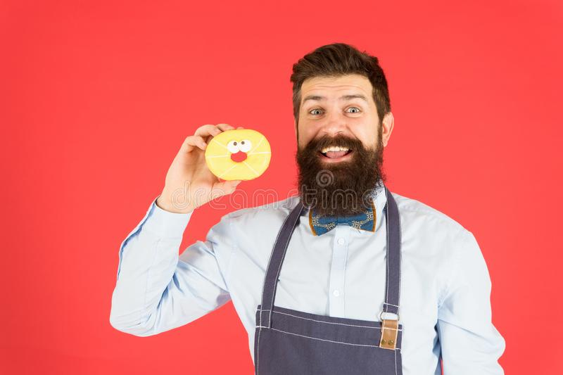 Glazed donut. Bearded well groomed man in apron selling donuts. Donut food. Baked goods. Sweets and cakes. Junk food. Hipster bearded baker hold donuts. Eat stock image