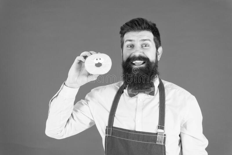 Glazed donut. Bearded well groomed man in apron selling donuts. Donut food. Baked goods. Sweets and cakes. Junk food stock image