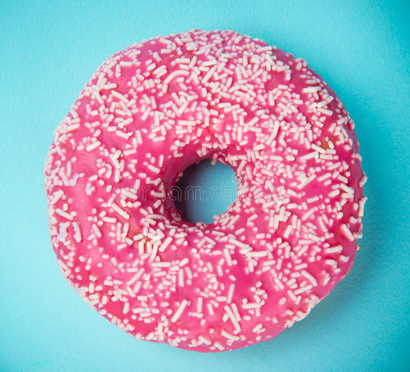 Glazed donut with colorful sprinkles on blue pastel background. Top view royalty free stock images