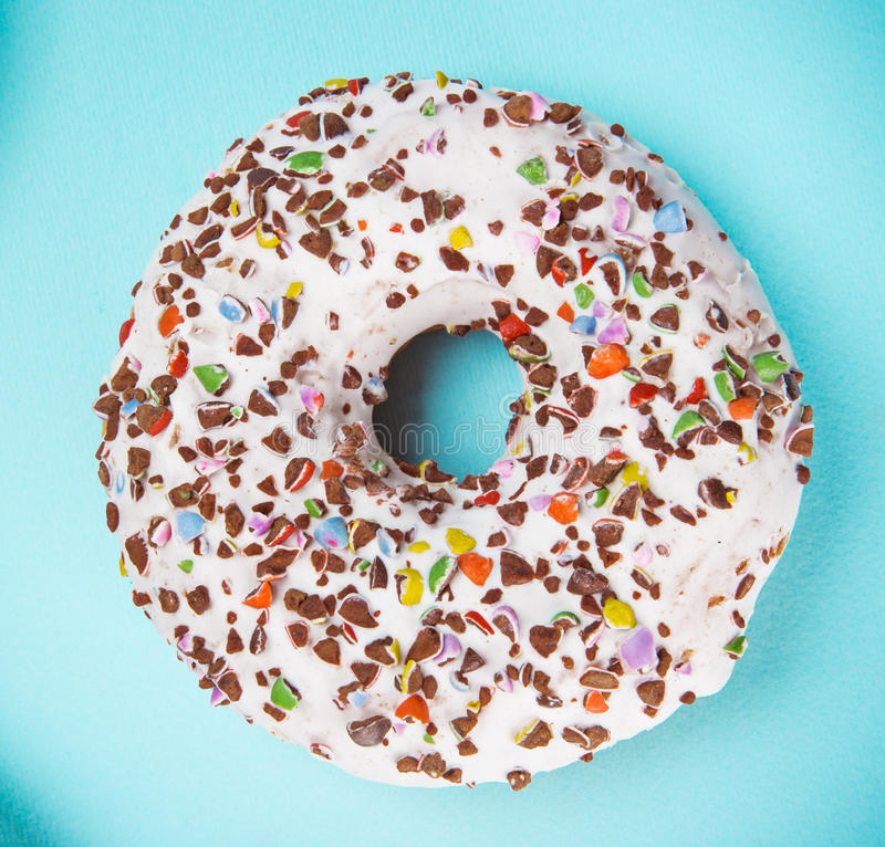 Glazed donut with colorful sprinkles on blue pastel background. Top view stock photos