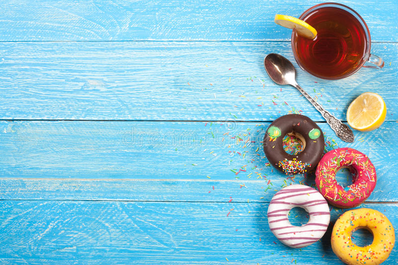 Glazed donuts with a cup of tea on a blue wooden background with copy space for your text. Top view.  royalty free stock photo