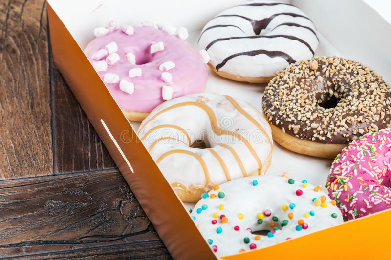 Glazed donuts with different fillings. In the box royalty free stock image