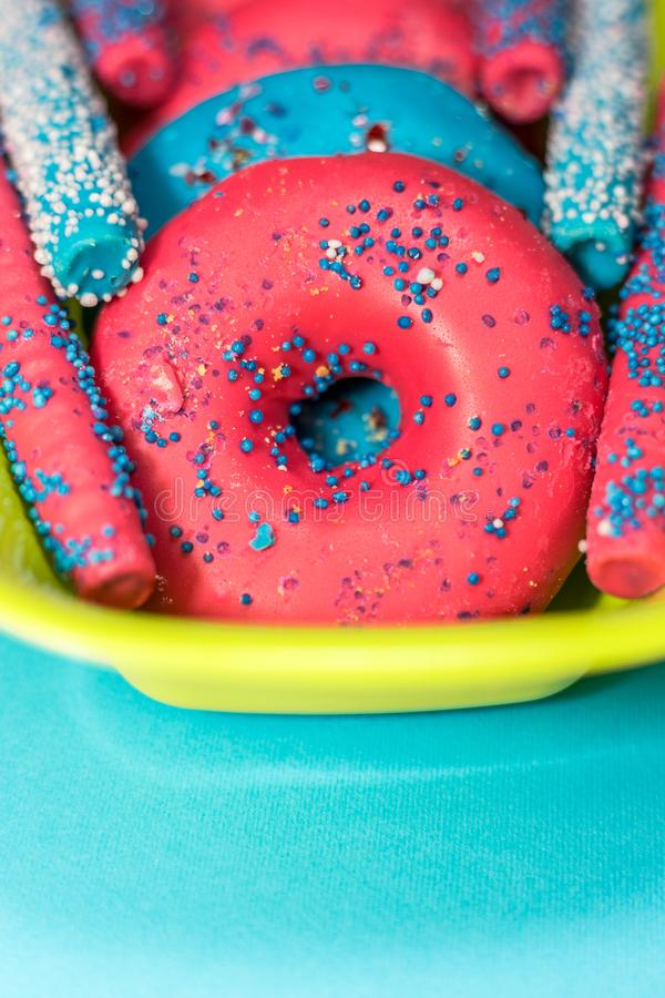 Glazed donuts with sprinkles and candy sticks on color background royalty free stock image