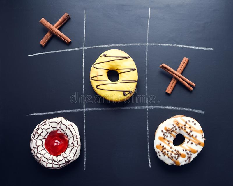 Glazed donuts tic-tac-toe game. Chalk drawing on a dark background. Creative food flat lay. Game noughts and crosses with donuts on chalkboard. Unhealthy diet royalty free stock image