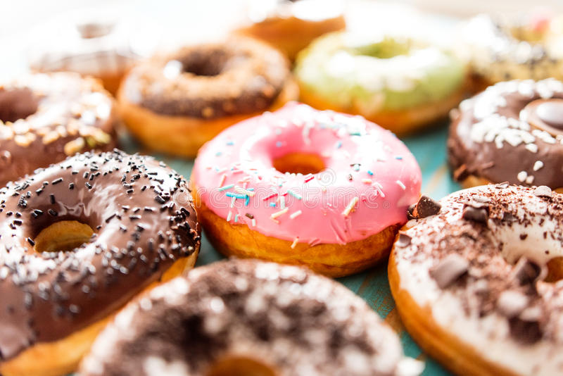 Glazed doughnuts with sprinkles. A lot of different colorful donuts. Chocolate, vanilla, caramel glazing and sprinkles, nuts and chocolate topping stock images
