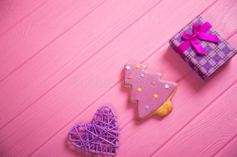 Glazed gingerbread in form of Christmas tree, purple wicked heart and gift box on pink wooden table royalty free stock images