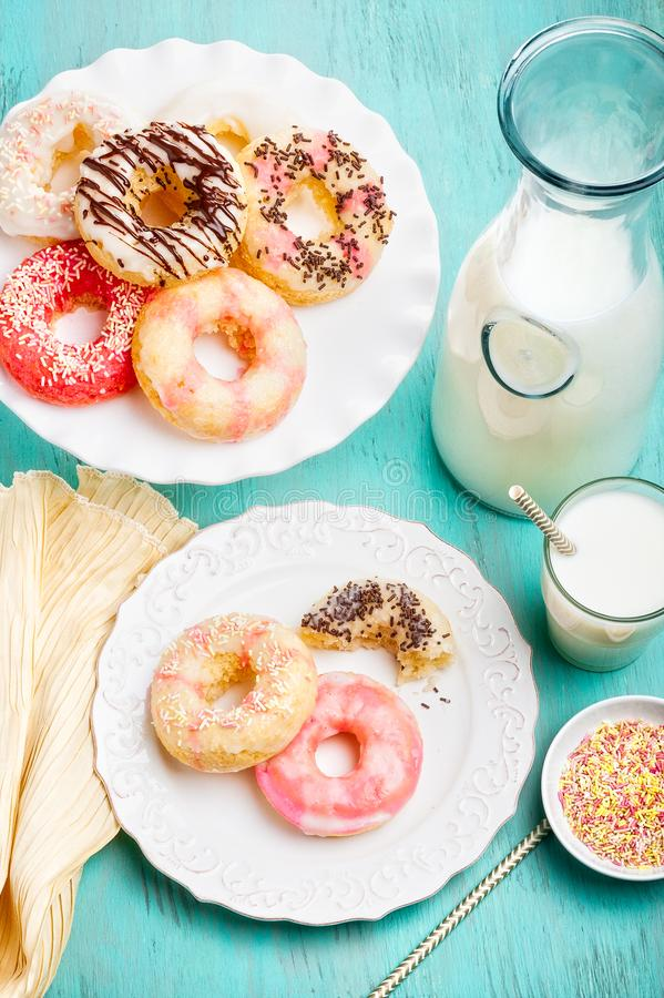 Glazed gluten free donuts with assorted sprinkles and drizzles. A cake plate and serving plate filled with glazed gluten free vanilla and chocolate glazed stock image