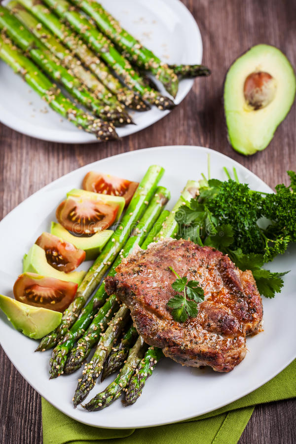 Glazed green asparagus with grilled pork chop royalty free stock images