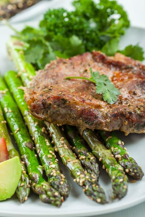 Glazed green asparagus with grilled pork chop stock photos