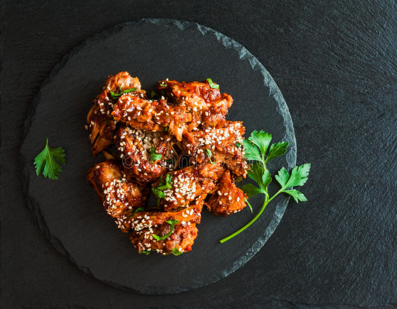 Glazed pork with homemade sauce made from onions, garlic, tomatoes, mustard, vinegar, honey, soy sauce and sesame seeds. Black stone background, fresh parsley royalty free stock images