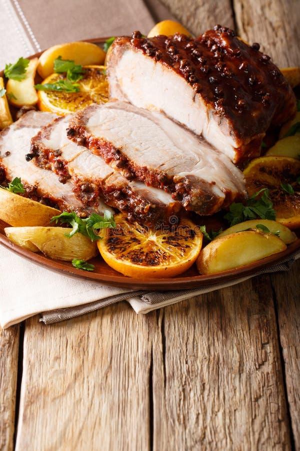 Glazed roast pork with potatoes, oranges and apples close-up. Vertical. Glazed roast pork with potatoes, oranges and apples close-up on a plate. Vertical stock image