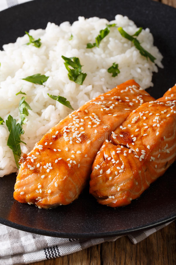 Glazed salmon fillet with rice garnish close-up. vertical. Glazed salmon fillet with rice garnish close-up on a plate. vertical stock photo