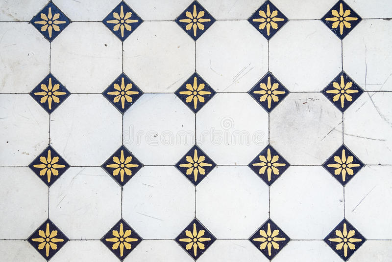 Glazed tiles. Pattern of old white tiles combined with small blue and yellow ones stock images