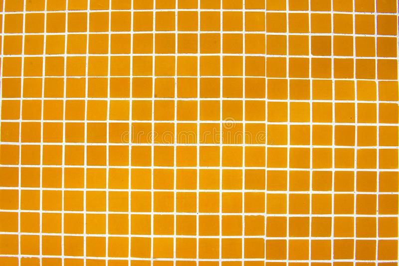 Glazed Tiles, Textures, Shiny and Tiny Square, Colorful. Shiny and tiny yellow/ reddish glazed tiles on house facade wall royalty free stock photography