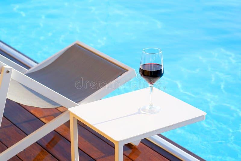 Glazen één rode wijn op de achtergrond van de pool royalty-vrije stock fotografie