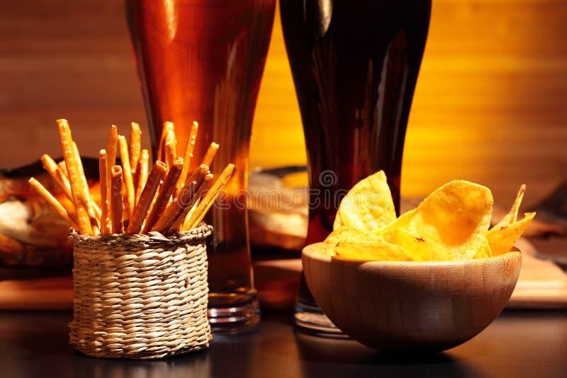 Glazen bier met spaanders en snacks stock afbeeldingen