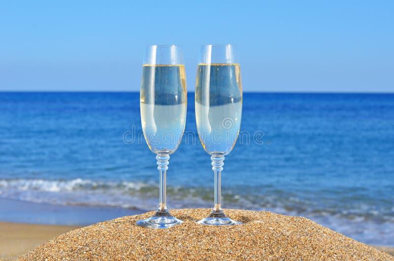 Glazen champagne op het strandzand stock afbeeldingen