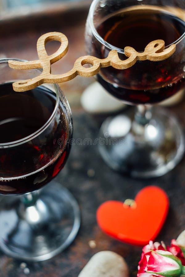 Glazen de dagwijn van Valentine met de de de brievenliefde, bloemen en harten stock afbeelding