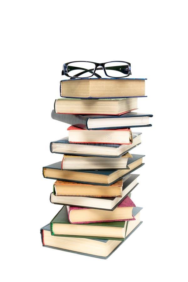Glazen die op een stapel van boeken liggen witte achtergrond - verticale ph stock foto's