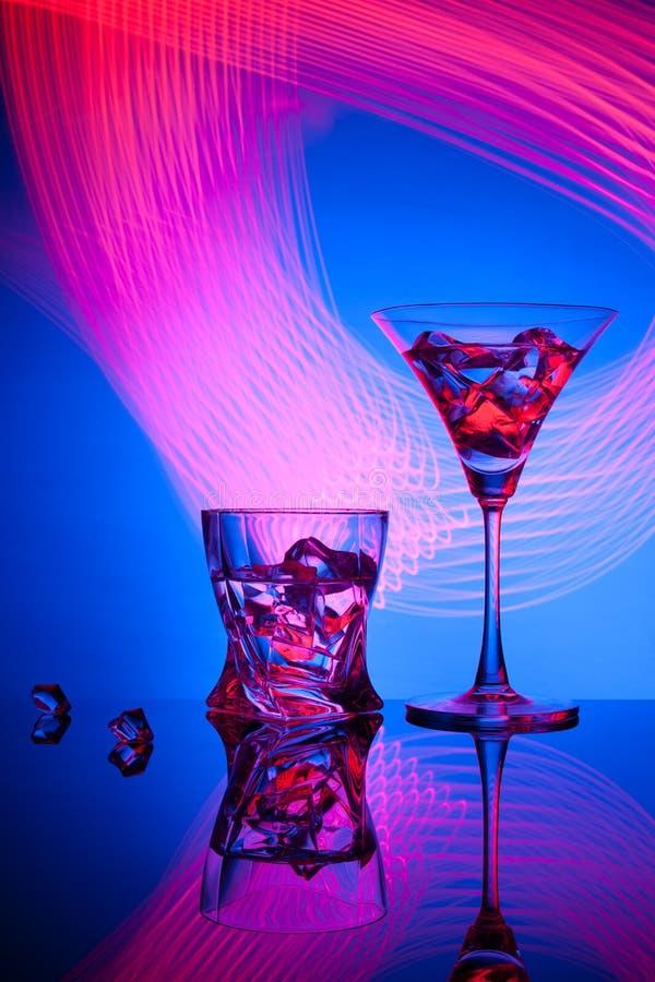 Glazen een de wiskyijs van cocktailmartini, tegen de rode achtergrond van mooie lichteffecten stock foto