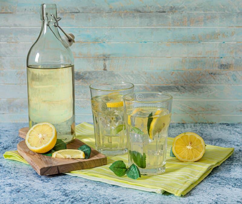 2 glazen en fles vers citroensap met muntbladeren royalty-vrije stock foto's