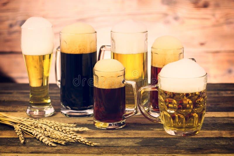 Glazen en mokken met verschillende bieren stock afbeelding