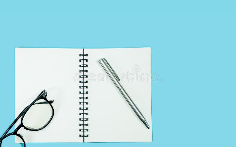Glazen en pen met leeg notitieboekje op blauwe achtergrond stock foto