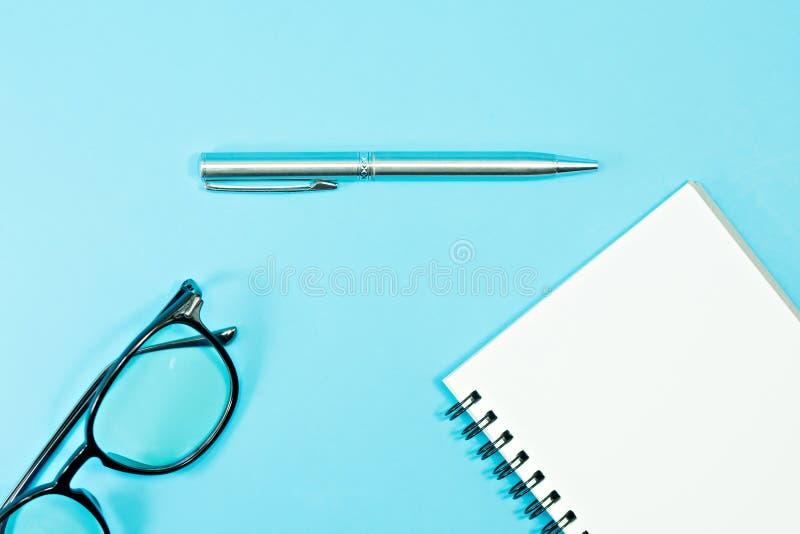 Glazen en pen met leeg notitieboekje op blauwe achtergrond royalty-vrije stock foto