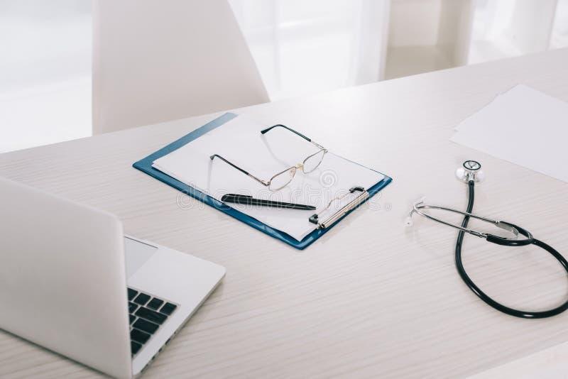 glazen en pen op klembord op werkende lijst royalty-vrije stock afbeelding