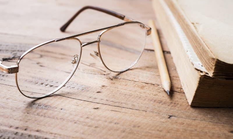 Glazen en potlood en oude boeken op houten lijstachtergrond stock foto