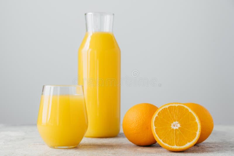 Glazen jus d'orange, gesneden verse sinaasappelen op witte achtergrond Horizontale samenstelling Heerlijke fruit en drank citrusv stock afbeelding