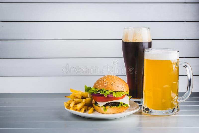 Glazen licht en donker bier met cheeseburger en Frieten op aluminiumpanelen royalty-vrije stock foto