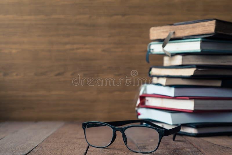 Glazen met boek met harde kaftboeken op houten lijst Vrije ruimte voor tekst stock afbeelding