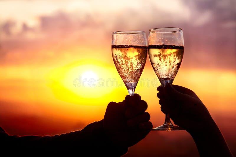 Glazen met champers bij zonsondergang stock afbeelding