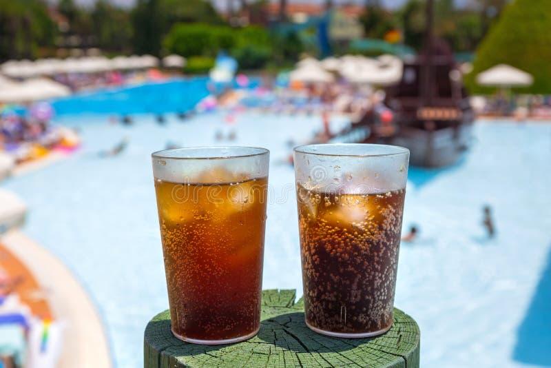 Glazen met kola en ijs bij de pool stock foto