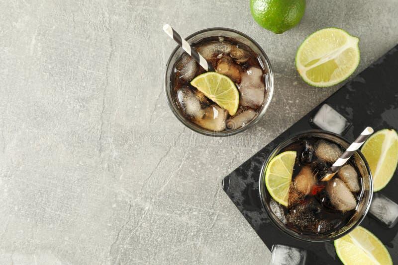Glazen met koude kola en citrusvrucht op grijze lijst stock afbeeldingen