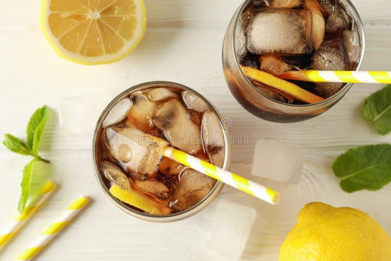 Glazen met koude kola en citrusvrucht op witte houten achtergrond stock afbeeldingen