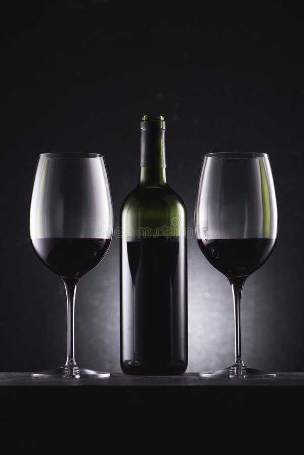 glazen met rode wijn en wijnfles worden gevuld in midden dat stock fotografie
