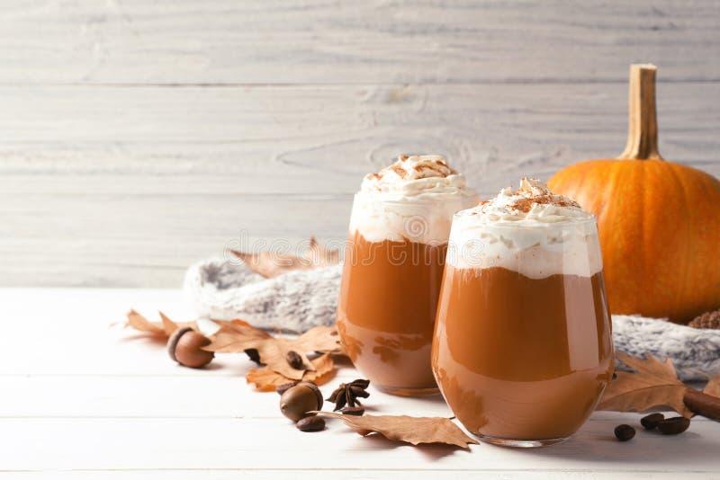 Glazen met smakelijk pompoenkruid latte op houten lijst royalty-vrije stock afbeeldingen