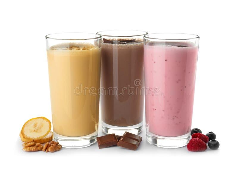 Glazen met verschillende eiwitschokken en ingrediënten stock afbeeldingen