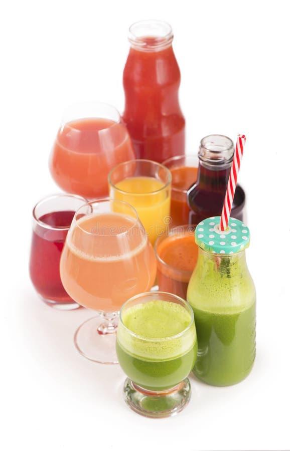 Glazen met verse organische die groente en vruchtensappen op wit worden geïsoleerd stock fotografie