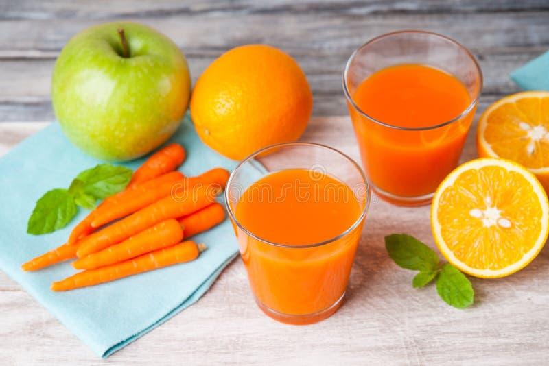 Glazen met wortelsap, appel, muntblad en gesneden sinaasappel royalty-vrije stock fotografie